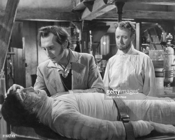 Baron Frankenstein played by Peter Cushing leans over the monster he has created Christopher Lee as Robert Urquhart looks on The scene is from 'The...