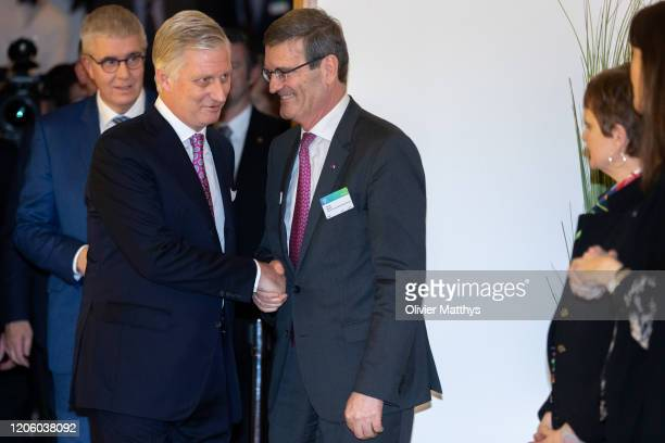 Baron Pieter Timmermans looks on as King Philippe of Belgium shakes hands with outgoing FEB chairman Bernard Gilliot during the 125th anniversary...