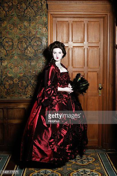 baroque lady in red dress before wood door leather wall - baroque stock pictures, royalty-free photos & images