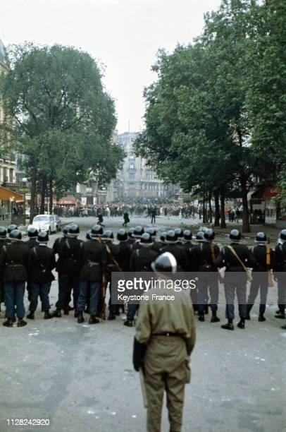 Barrage de CRS bloquant la manifestation étudiante dans le quartier latin, derrière le barrage, un militaire regarde, à Paris, France, le 25 mai 1968.