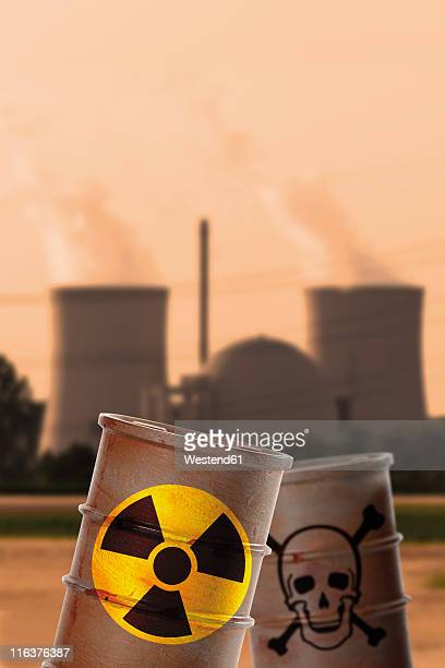 Barrels with signs of skull and crossbones and radioactivity in front of nuclear power reactor