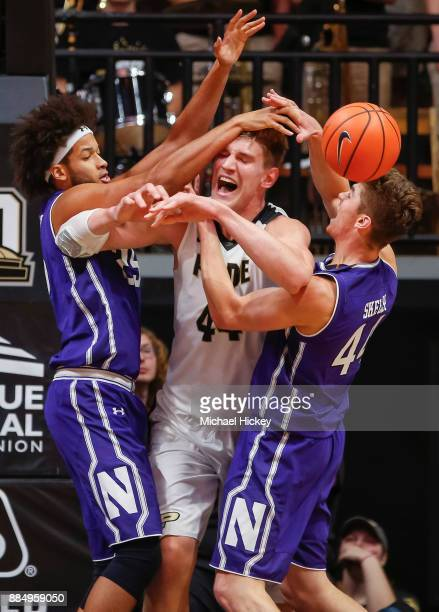 Barret Benson and Gavin Skelly of the Northwestern Wildcats double team Isaac Haas of the Purdue Boilermakers and cause him to lose the ball at...