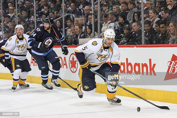 Barret Jackman of the Nashville Predators plays the puck along the boards away from Anthony Peluso of the Winnipeg Jets during first period action at...