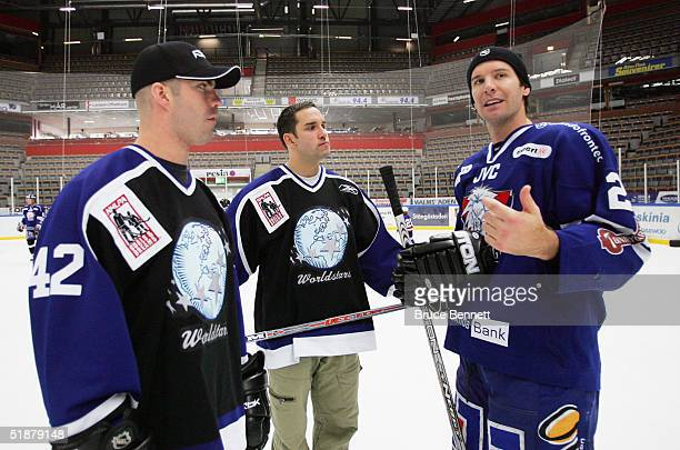 Barrett Jackman and Alexandre Daigle of the Primus Worldstars meet up with Mike Knuble of Linkoping HC at a family skate party on December 19 2004 at...