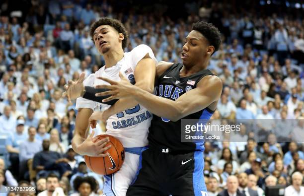 Barrett of the Duke Blue Devils battles for a loose ball against Cameron Johnson of the North Carolina Tar Heels during their game at Dean Smith...