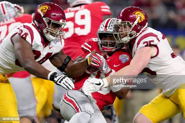 T Barrett of the Ohio State Buckeyes carries the ball against Rasheem Green of the USC Trojans and Cameron Smith of the USC Trojans in the first...