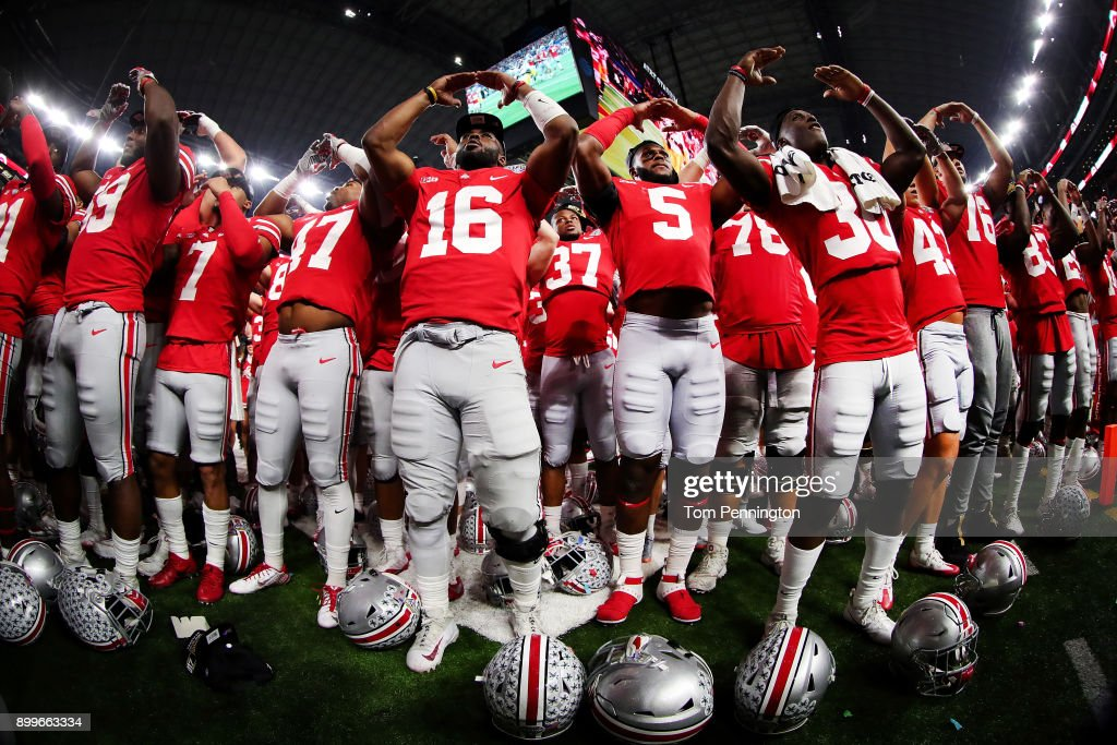 J.T. Barrett #16 of the Ohio State Buckeyes celebrates with his team after the Ohio State Buckeyes beat the USC Trojans 24-7 during the Goodyear Cotton Bowl Classic at AT&T Stadium on December 29, 2017 in Arlington, Texas.
