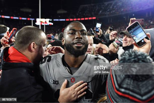 T Barrett of the Ohio State Buckeyes is surrounded by fans as he walks off the field after defeating Penn State 3938 at Ohio Stadium on October 28...