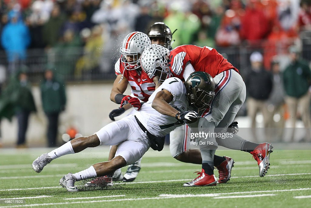 J.T. Barrett #16 of the Ohio State Buckeyes looks to run the ball in the third quarter and is tackled by Demetrious Cox #7 of the Michigan State at Ohio Stadium on November 21, 2015 in Columbus, Ohio.