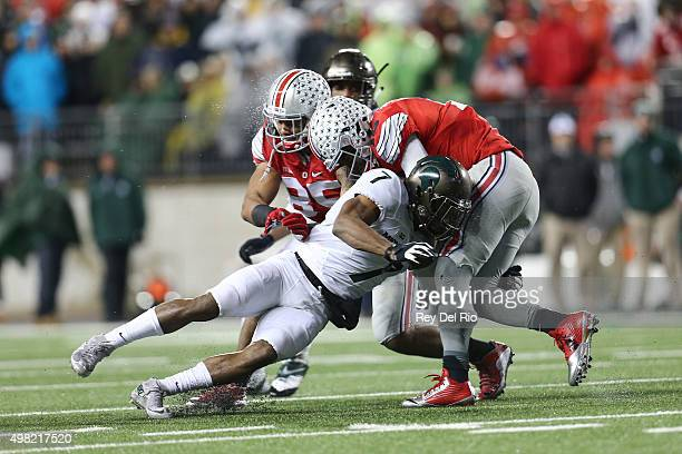 T Barrett of the Ohio State Buckeyes looks to run the ball in the third quarter and is tackled by Demetrious Cox of the Michigan State at Ohio...