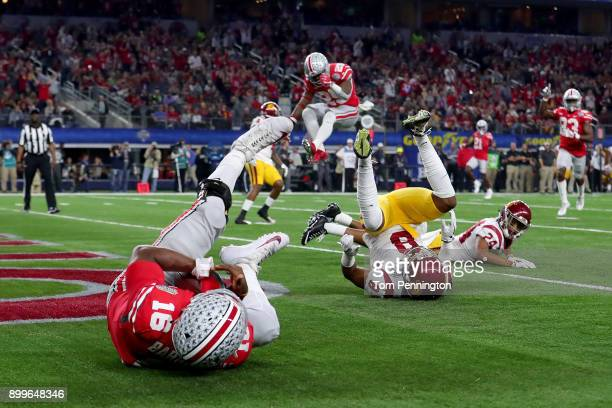 T Barrett of the Ohio State Buckeyes scores a touchdown against Iman Marshall of the USC Trojans in the first half during the Goodyear Cotton Bowl...