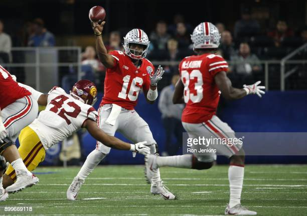 T Barrett of the Ohio State Buckeyes throws while under pressure from Uchenna Nwosu of the USC Trojans in the second half of the 82nd Goodyear Cotton...