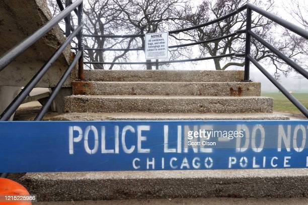 Barricade blocks a pedestrian bridge that leads to the Lake Michigan shoreline on March 27, 2020 in Chicago, Illinois. Upset by residents continuing...