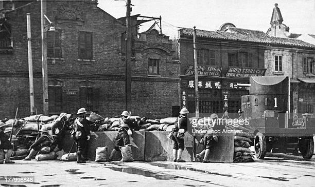 A barricade put up by the Shanghai volunteer corps at North Honan Road An armored car is there for reinforcements Shanghai China February 22 1932