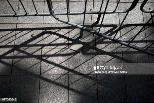 barricades cast shadows on a pavement - barricade stock photos and pictures