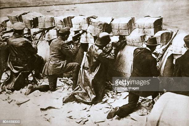 Barricades on a street German Revolution Berlin Germany c1918c1919 Civilians and soldiers in position behind defences made from bundles of newspapers...