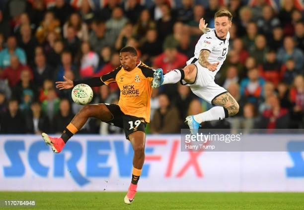 Barrie McKay of Swansea City competes for the ball in the air with Reggie Lambe of Cambridge United during the Carabao Cup Second Round match between...