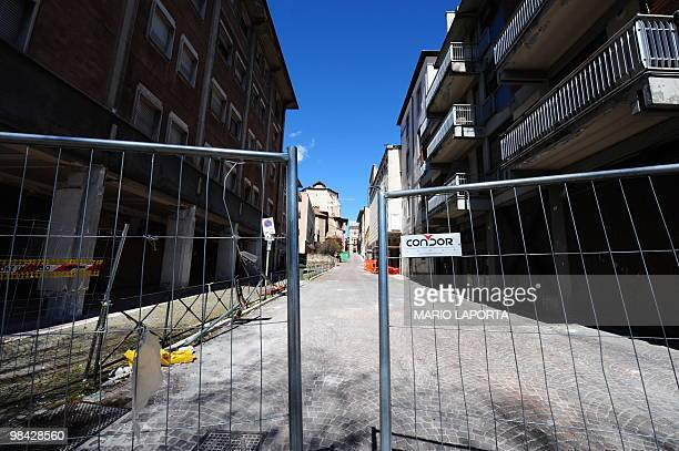 A barrier blocks the entrance the entrance in a street of destroyed buildings on the day of the first anniversary of the earthquake that devastated...