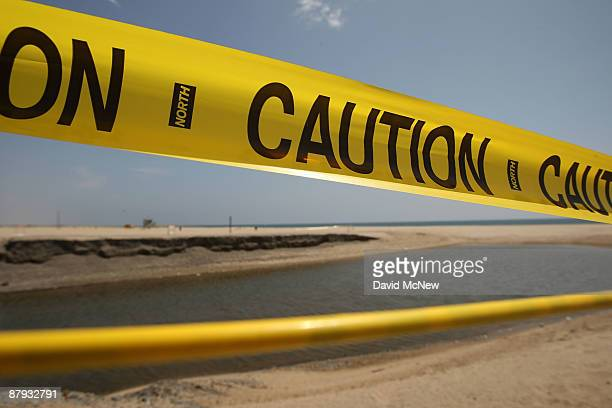 A barrier of caution tape warns beachgoers to stay out of the water which is polluted by runoff from a nearby storm drain and creek at Will Rogers...