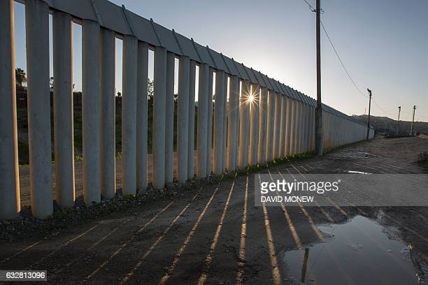 A barrier of concrete columns stands among multiple layers of steel walls fences razor wire and other barricades along the US Mexico border crossing...