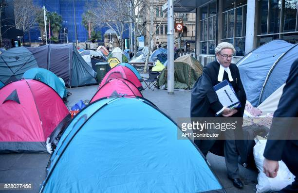 A barrister walks between tents set up in Martin Place which has become known as 'Tent City' as homeless people set up camp in the central business...