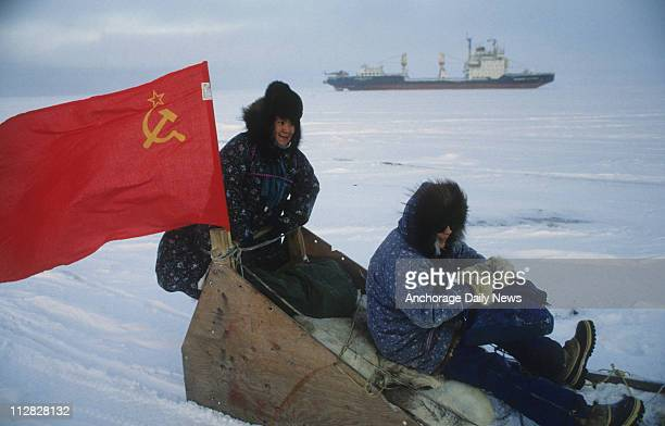 Barrow residents ride a sled drawn by a snowmachine as the Soviet icebreaking cargo ship Vladimir Arsenev makes a path through the ice pack off Point...