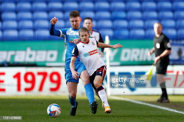 Barrows Scott Quigley challenges Boltons Lloyd Isgrove during the Sky Bet League 2 match between Bolton Wanderers and Barrow at the Reebok Stadium,...