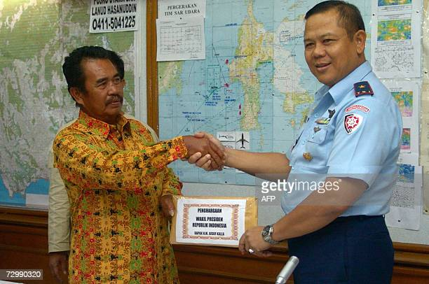 Air Marshal Eddy Suyanto hands over a reward to Indonesian fisherman Bakrie who was the first to find wreckage of the crashed Adam Air aircraft...