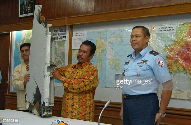 Indonesian fisherman Bakrie holds up part of the Adam Air aircraft as Air Marshal Eddy Suyanto stands by during a press conference in Barru 13...