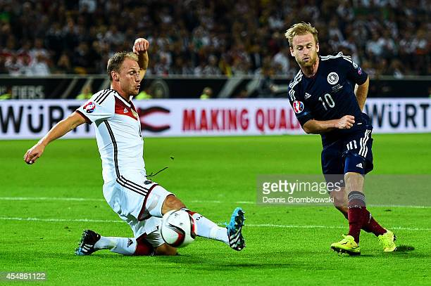 Barry Bannan of Scotland is blocked by Benedikt Howedes of Germany during the EURO 2016 Group D qualifying match between Germany and Scotland at...