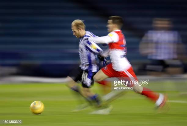 Barry Bannan of Sheffield Wednesday is pulled back by Andronicos Georgiou of Wycombe Wanderers during the Sky Bet Championship match between...
