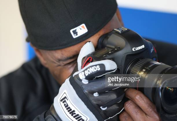 Barry Bonds of the San Francisco Giants looks through a camera in the dugout during batting practice against the Milwaukee Brewers during a Major...