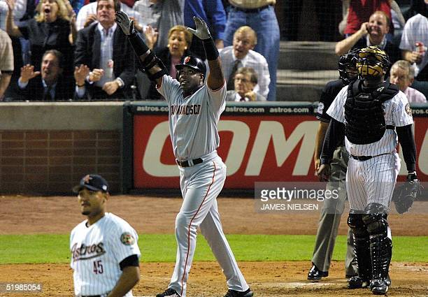 Barry Bonds of the San Francisco Giants watches along with umpire Alfonso Marquez Houston Astros pitcher Wilfredo Rodriguez and catcher Tony Eusebio...
