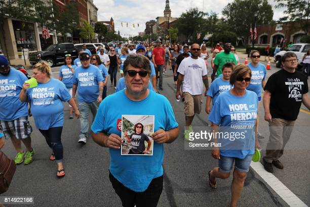 Barry Bova holds a picture of his son Brad who died of a heroin overdose while marching through the streets of Norwalk against the epidemic of heroin...