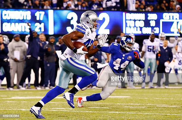 Barry Church of the Dallas Cowboys carries the ball after intercepting a pass by Eli Manning of the New York Giants in the third quarter at MetLife...