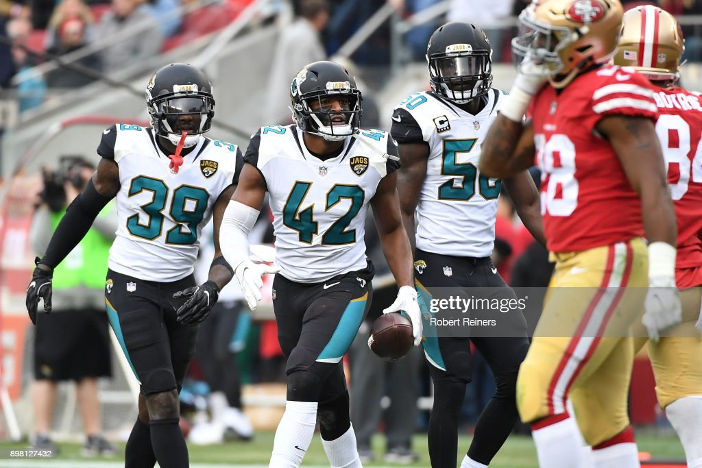 Barry Church #42 of the Jacksonville Jaguars celebrates with Tashaun Gipson #39 and Telvin Smith #50 of the Jacksonville Jaguars after an interception of Jimmy Garoppolo #10 of the San Francisco 49ers in the end zone during their NFL game at Levi's Stadium on December 24, 2017 in Santa Clara, California.