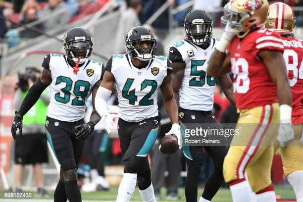 Barry Church of the Jacksonville Jaguars celebrates with Tashaun Gipson and Telvin Smith of the Jacksonville Jaguars after an interception of Jimmy...