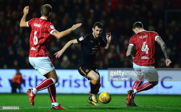 Barry Douglas of Wolverhampton Wanderers is tackled by Nathan Baker and Aden Flint of Bristol City during the Sky Bet Championship match between...