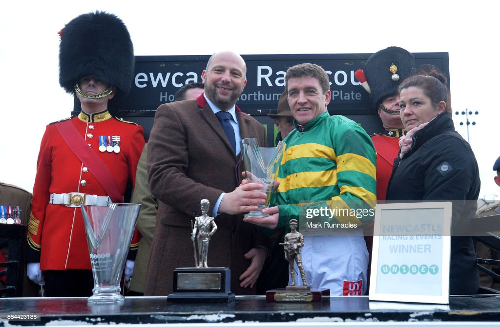 Barry Geraghty (R2), is presented with a trophy after winning the Unibet Fighting Fifth Hurdle Race (Class 1, Grade 1), riding Buveur D'Air at Newcastle Racecourse on December 2, 2017 in Newcastle upon Tyne, England.