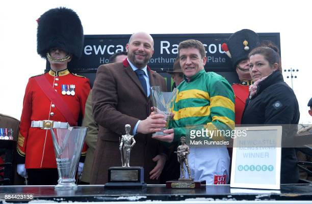 Barry Geraghty is presented with a trophy after winning the Unibet Fighting Fifth Hurdle Race riding Buveur D'Air at Newcastle Racecourse on December...