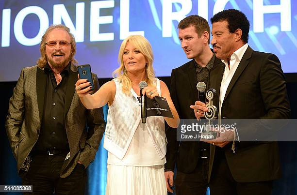 Barry Gibb Gaby Roslin guest and Lionel Richie take a selfie on stage during the Nordoff Robbins O2 Silver Clef Awards on July 1 2016 in London...