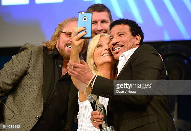Barry Gibb Lionel Richie and Gaby Roslin take a selfie on stage during the Nordoff Robbins O2 Silver Clef Awards on July 1 2016 in London United...