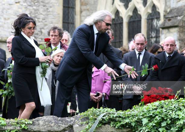 Barry Gibb places a rose on his brother's coffin watched by his wife Linda Gibb at the funeral of Robin Gibb held at St Mary's Church Thame on June 8...