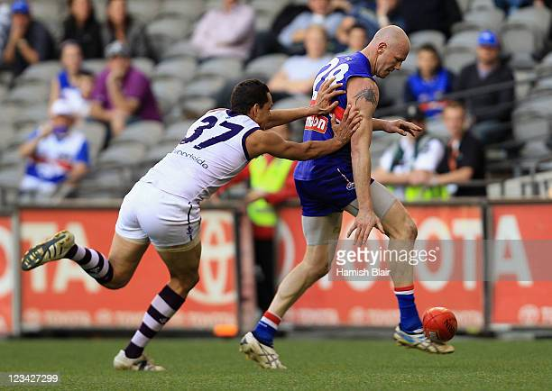 Barry Hall of the Bulldogs kicks his last AFL goal with pressure from Michael Johnson of the Dockers during the round 24 AFL match between the...