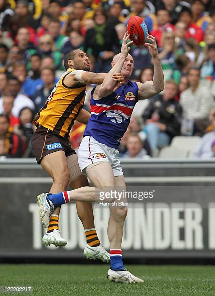 Barry Hall of the Bulldogs marks under pressure from Josh Gibson of the Hawks during the round 23 AFL match between the Hawthorn Hawks and the...