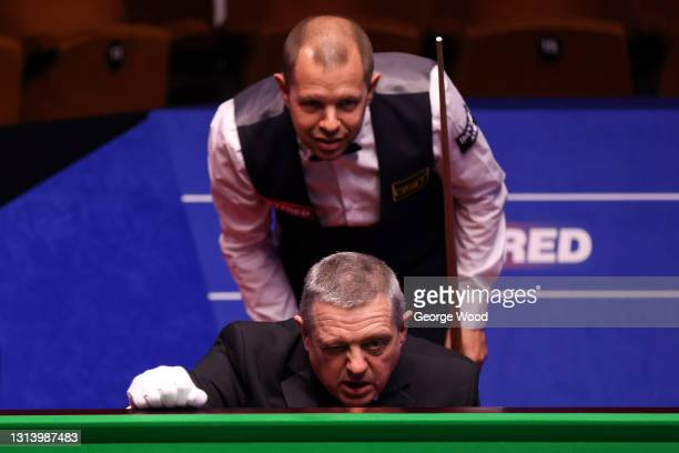 Barry Hawkins of England and referee, Rob Spencer, check the positioning of the ball during the Betfred World Snooker Championship Round Two match...