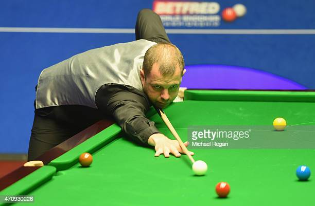 Barry Hawkins of England plays a shot against Mark Allen of Northern Ireland during day seven of the 2015 Betfred World Snooker Championship at...