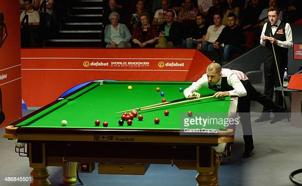 Barry Hawkins plays a shot against Ricky Walden during their second round match in The Dafabet World Snooker Championship at Crucible Theatre on...