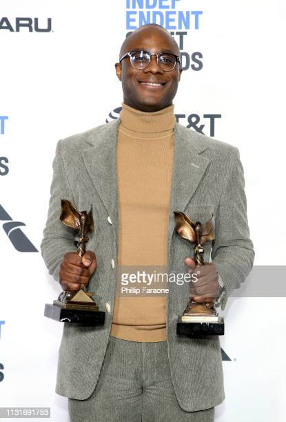 "Barry Jenkins poses in the press room with the Best Director and Best Feature awards for the film ""If Beale Street Could Talk"" during the 2019 Film..."