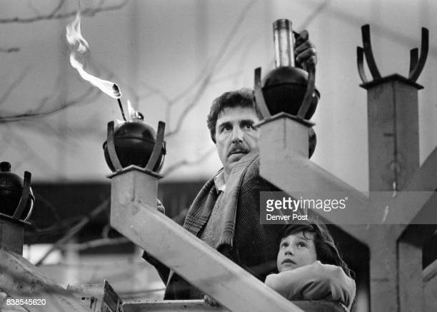 Barry Karp designer of the Menorah on 16th St tests the lanterns prior to the lighting ceremony Meagan Gold daughter of his partner rode up in the...